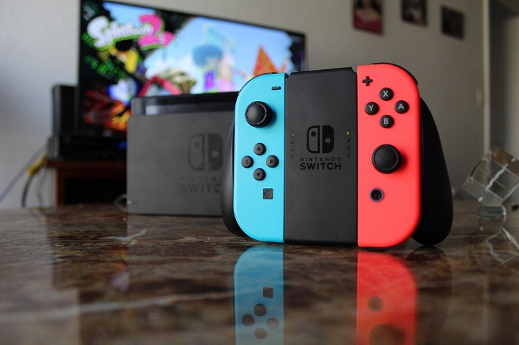 Console nintendo switch (avec manette) devant un écran tv